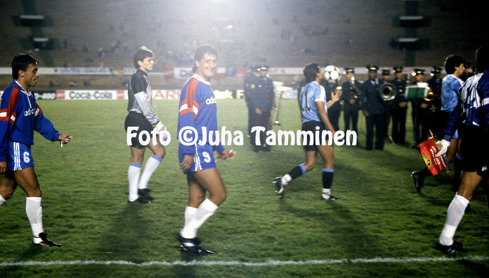 Copa America - Brasil 1989<br /> 6.7.1989, Estadio Serra Dourada, Goi&acirc;nia. <br /> Group B, Chile v Uruguay.<br /> Juan Carlos Letelier (Chile) smiling at the camera as team walk to form for the anthems before the match. On left Jaime Pizarro, on the background Javier Zeoli and Ruben Sosa of Uruguay.
