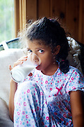 Young girl drinking a glass of milk in her pajamas.