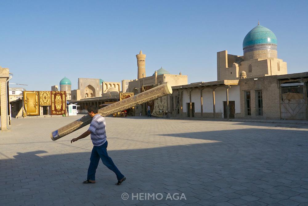 Uzbekistan, Bukhara.<br /> Carpets in front of Kalon Ensemble.