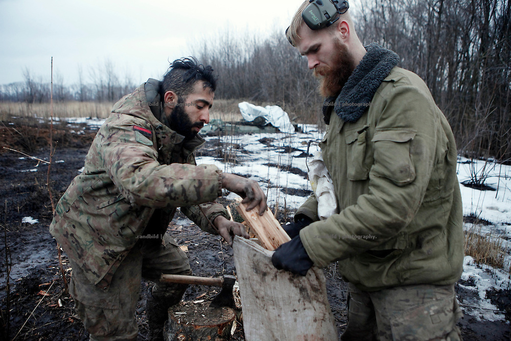 Ben (le.) and Craig fill a bag with wet fire wood for their trench position close by at the donetsk frontline.<br />