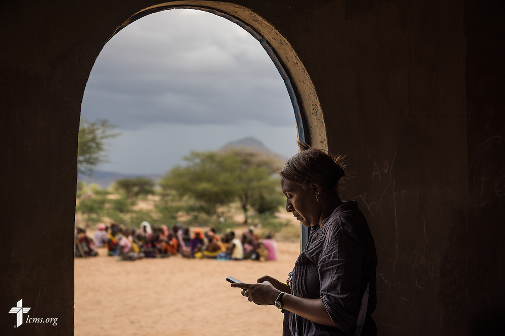 Shara Cunningham, career missionary in Eastern and Southern Africa, checks her smartphone during the LCMS Mercy Medical Team on Tuesday, June 21, 2016, in Nataparkakono, a village in Turkana, Kenya.  Cunningham coordinates logistics for different teams and projects. LCMS Communications/Erik M. Lunsford