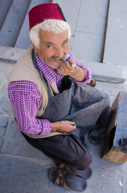 An old shoe shiner smoking a cigarette in the old town of Gaziantep, southeastern Turkey.