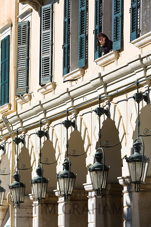 Woman at window above arcades and traditional lanterns of famous The Liston at the Spianada in Kerkyra, Corfu Town, Greece