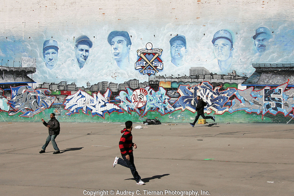 The Bronx, NY-- March 9, 2008: In the shadow of Yankee Stadium a mural of Yankee legends watches over young men who play a parking lot game of baseball.
