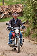 Man riding motorcyle through village of Misminay; Sacred Valley, Urubamba Province, Peru.