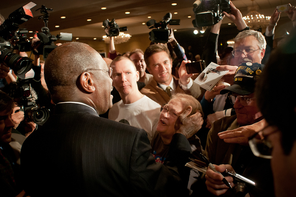 Presidential hopeful Herman Cain surrounded by a media crush tries to greet supporters after speaking at a  campaign Rally in the Radisson Hotel in Nashua, NH.