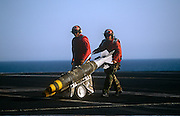 Red shirted ordnance men prepare to fit smart bombs to an F/A-18 fighter jet on deck of USS Harry S Truman. The Truman is the largest and newest of the US Navy's fleet of new generation carriers, a 97,000 ton floating city with a crew of 5,137, 650 are women.