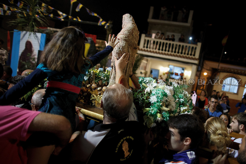 15/08/2016. Fishermen carry the image of the Virgin of Palm back to the sea as a girl touches it at El Rinconcillo beach during the yearly Virgin of Palm maritime pilgrimage on August 15, 2016 in Algeciras, Spain. The Our Lady of Palm maritime pilgrimage in Algeciras dates back to 1975 and takes place annually when fishermen rescue the submerged virgin from the deep sea. Worshippers amid thousands of visitors await its arrival at the Rinconcillo beach. The devotion for the Virgin of Palm comes from the seventeenth century when a ship coming from Italy docked at Algeciras port to wait out bad weather. According to legend, once the crew of the ship removed a box with an image of the Virgin from its cargo the weather turned and the sea's tides were calmed. (© Pablo Blazquez)