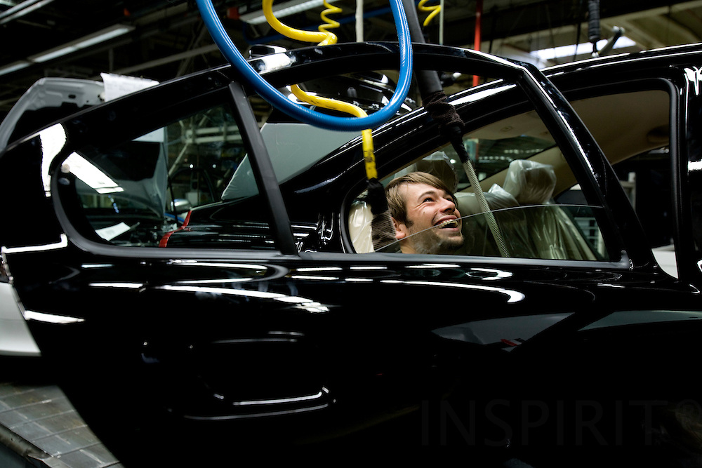 GHENT - BELGIUM - 13 NOVEMBER 2008 -- Volvo Cars Gent -- A worker laughs while doing the final finish to the hind door on a new Volvo car at the assembly line.  Photo: Erik Luntang/INSPIRIT Photo