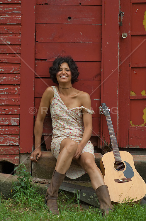 African American woman sitting with her guitar smiling