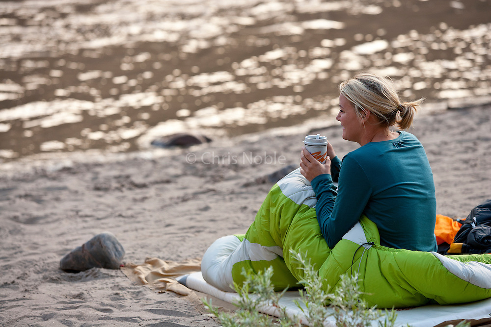 Kate Harvey wakes up after sleeping on the beach along the Colorado River in Westwater Canyon, Utah.