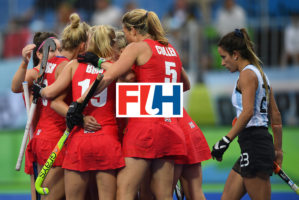 TOPSHOT - Britain team members celebrate a goal as Argentina's Maria Campoy walks past during the women's field hockey Britain vs Argentina match of the Rio 2016 Olympics Games at the Olympic Hockey Centre in Rio de Janeiro on August, 10 2016. / AFP / MANAN VATSYAYANA        (Photo credit should read MANAN VATSYAYANA/AFP/Getty Images)