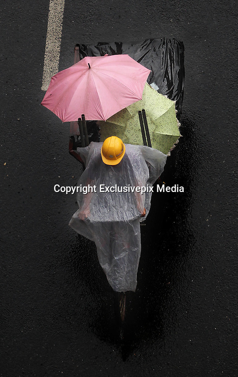 GUANGZHOU, CHINA <br /> <br /> Life On The Tricycle<br /> <br /> A porter rides a tricycle carrying cloths and people at Guangzhou International Textile City in Guangzhou, Guangdong Province of China. More than 1,500 tricycles are active in the business district. <br /> ©Exclusivepix Media