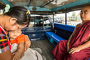 "24 MAY 2013 - MAE SOT, THAILAND:    A Burmese woman and her child with a Burmese Buddhist monk in the back of a ""songthaew"" going to Mae Sot, Thailand. A ""songthaew"" is a pickup truck converted to use as a bus. They're common in Southeast Asia.  PHOTO BY JACK KURTZ"