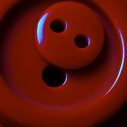 macro of two red buttons nestled on top of each other cropped to square format