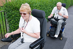 Disabled couple out in the street using mobile phones to communicate with one another,