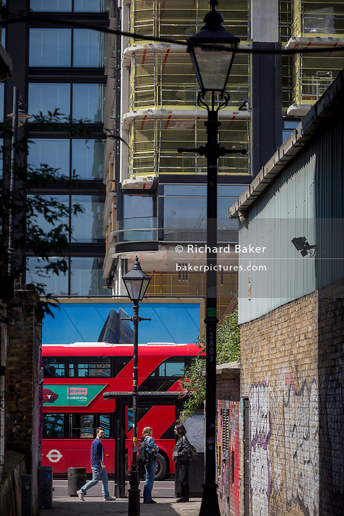 Young women talk in an graffiti alleyway opposite a London bus and a construction hoarding showing the Foster-designed Principal Tower that's under construction on Shoreditch High Street, on 10th May 2017, in London, England.