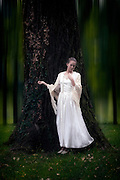 a girl in a period dress is leaning at a tree