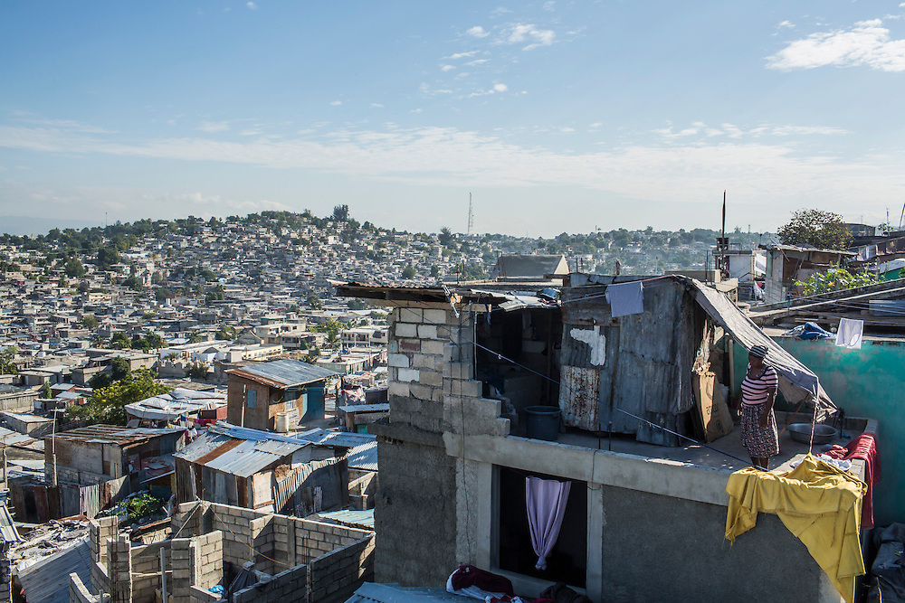 A woman stands on her rooftop in the Fort National neighborhood on Tuesday, December 16, 2014 in Port-au-Prince, Haiti. One of Port-au-Prince's poorer neighborhoods, Fort National was among the hardest hit by the 2010 earthquake. Still, its residents lack electricity or running water, and only several new homes have been built by aid organizations and the government, despite years of promises.
