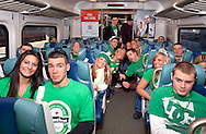 """MARCH 17, 2011 - LONG ISLAND NY: Dressed for St. Patrick's Day in green, young adults riding Long Island Railroad LIRR to Penn Station to celebrate in Manhattan, NY, USA, morining of St. Patrick's Day. At top of exit, words """"Penn Station"""" appear in red on electric sign announcing next station stopping at.The LIRR added more than a dozen trains to Manhattan for St. Patrick's Day Parade. At rear, ads for (left) ING Direct and (right) New York Lottery. Train at Jamaica Station stop. For St. Patrick's Day safety, alcohol was forbidden in train cars, on platform and train station. EDITORIAL USE ONLY)"""