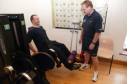 Access to services,  Fitness instructor and disabled man in the gym using; Leg Extension,