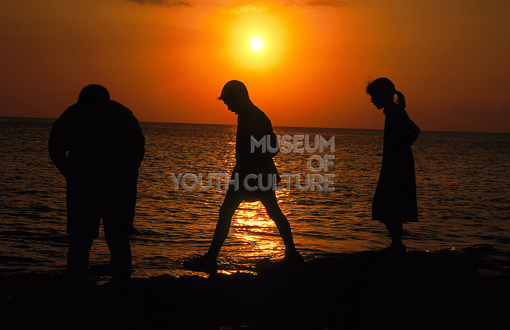 Three silhouetted figures on a beach Ibiza 1990's