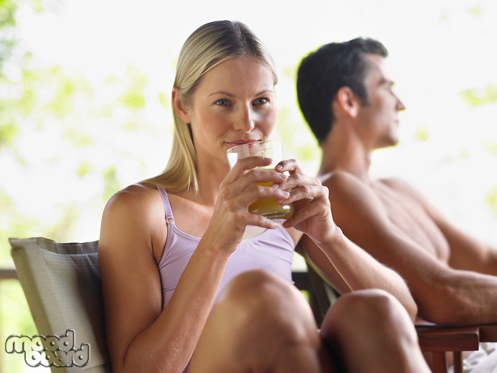 Couple sitting outdoors woman drinking juice focus on foreground