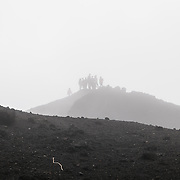 A group of tourists stands on top of one of the outcrops at the summit of Pacaya Volcano and is partially shrouded by the mix of cloud and steam. Pacaya is an active volcano that forms part of the Central America Volcanic Arc. It forms a popular tourist destination easily accessible from Antigua and Guatemala City. Situated within the Pacaya National Park, it rises to 2,552 metres (8,373 ft). Its last major eruption, which caused considerable damange to nearby villages and reshaped the summit, was in May 2010. That eruption and scattered volcanic ash over much of the nearby area, prompting school closings and emergency evacuations and cleared much of the vegetation near the top of the mountain.