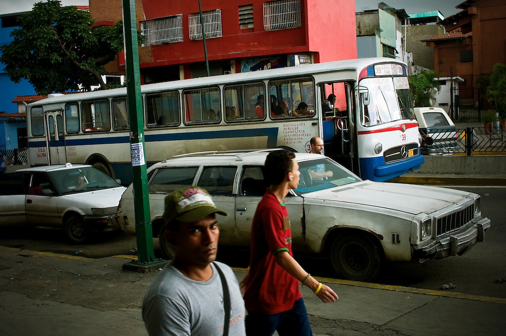 Men walk past a 1975 Chevy Malibu Wagon in Catia, a large slum in Caracas, Venezuela. Despite being gas guzzlers, American made cars from the 1970's are popular here because gas is inexpensive and the cars are affordable and durable on poorly maintained Venezuelan roads.