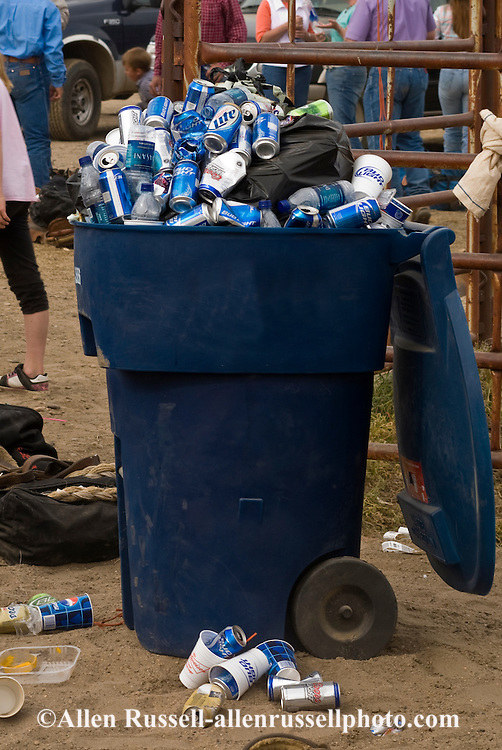 Trash can overflowing with beer cans
