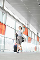 Full length of young businesswoman with luggage rushing in railroad station
