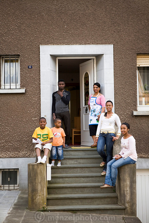 Maria Natercia Lopes-Furtado, and her husband Ernesto Lopes Sanchez, of Rodange, Luxembourg, and their four children: Darlene, Melody, Teddy, and Lionel, on the front steps of their home in the Grand Duchy of Luxembourg. The image is part of a collection of images and documentation for Hungry Planet 2, a continuation of work done after publication of the book project Hungry Planet: What the World Eats.