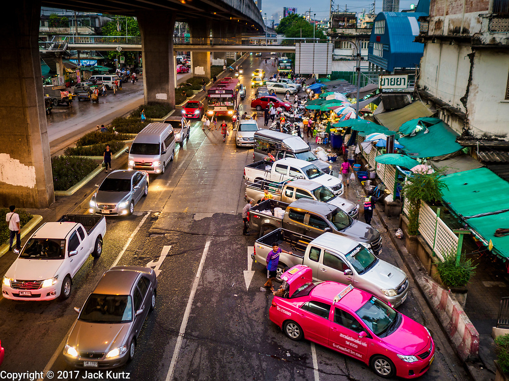 08 JUNE 2017 - BANGKOK, THAILAND: Morning traffic in front of Khlong Toey Market, Bangkok's main fresh market. Thai consumer confidence dropped for the first time in six months in May following a pair of bombings in Bangkok, low commodity prices paid to farmers and a sharp rise in the value of the Thai Baht versus the US Dollar and the EU Euro. The Baht is surging because of political uncertainty, related to Donald Trump, in the US and Europe. The Baht's rise is being blamed for a drop in Thai exports. This week the Baht has been trading at around 33.90 Baht to $1US, it's highest point in two years.      PHOTO BY JACK KURTZ