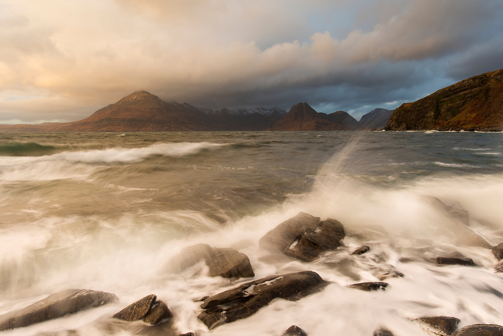 Waves crashing over rocky coastline near Elgol with view to Cuillin mountains, Isle of Skye, Scotland