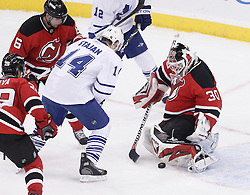 Jan 29, 2010; Newark, NJ, USA; New Jersey Devils goalie Martin Brodeur (30) makes a save while Toronto Maple Leafs center Matt Stajan (14) looks for the rebound during the third period at the Prudential Center. The Devils won 5-4 in overtime.