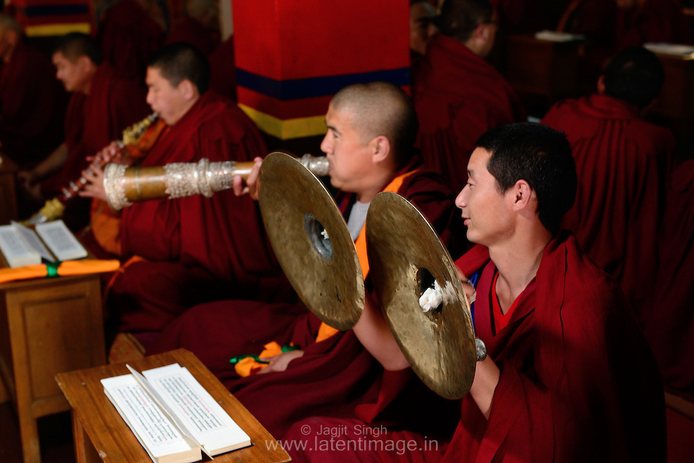 Monks playing a ritual sound instrument during the ritual prayer in a religious ceremony at the Tibetan YungDrung Bon Monastery at Dolanji.
