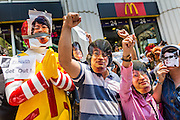 25 MAY 2014 - BANGKOK, THAILAND:  Thais wear a mask of Sombat Boonngam, a Red Shirt leader in hiding and still free from arrest, during a protest at a McDonald's in Bangkok. Public opposition to the military coup in Thailand grew Sunday with thousands of protestors gathering at locations throughout Bangkok to call for a return of civilian rule and end to the military junta.    PHOTO BY JACK KURTZ