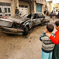 ERBIL, NORTHERN IRAQ - MARCH 20:  Two boys are overlooking the scene of an explosion in a passenger car in Erbil.  Unconfirmed reports suggest that the car was loaded with weapons and grenades when it exploded adding to the tension already existent in Erbil. (Photo Patrick Barth/Getty Images)