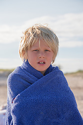 little boy wrapped in a towel at the beach
