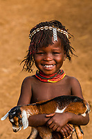 Young Nyangatom tribe girl holding a goat, Omo Valley, Ethiopia.
