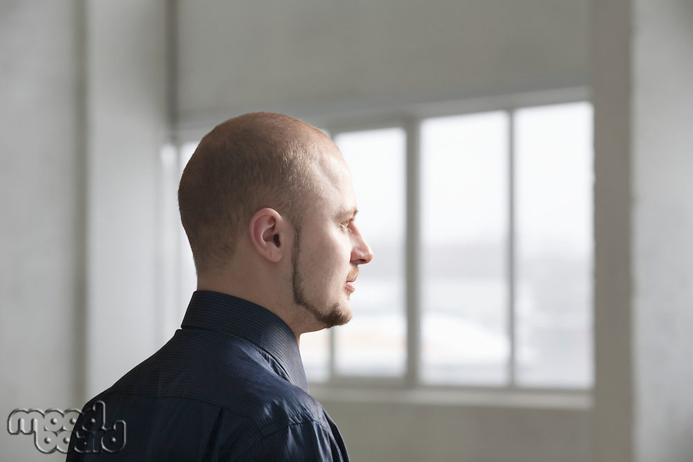 Profile of young businessman in warehouse interior