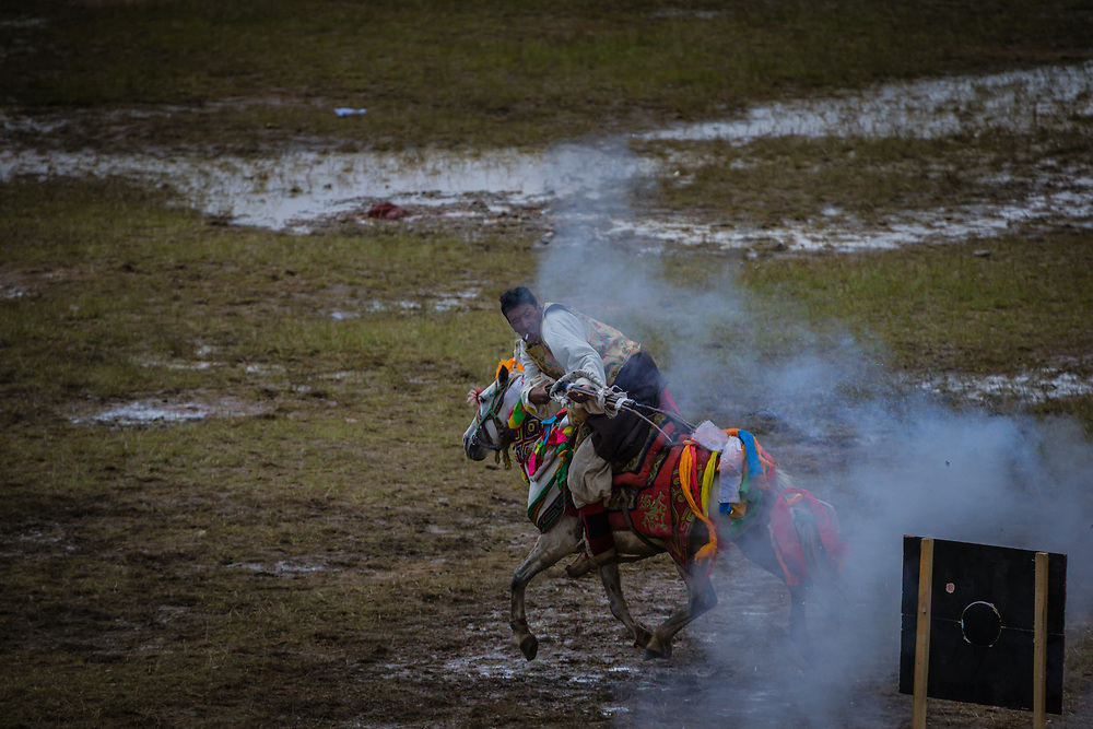 Nagchu Tibet. Rider competing on horse. Has to ride and to shoot with a prehistoric gun which risks to explode in his hands when he shoots.