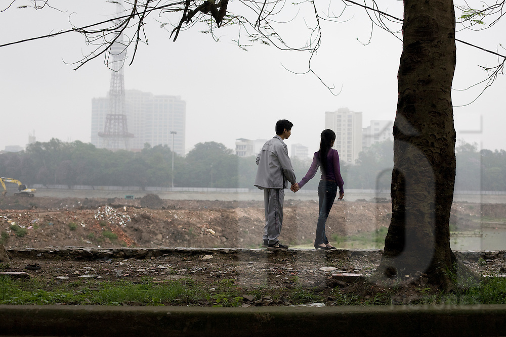 A young vietnamese couple is dating, holding each other's hand and over looking the place. Lenin park, hanoi, Vietnam, Asia.