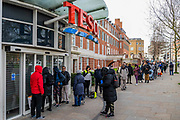 Some are masked but there is no social distancing - A queue waits patiently for the Tescos at Clapham South due to Coronavirus (Covid 19) shortages - tescos has introduced rationing which oddly, for example, allows people to buy 27 toilet rolls but only 2 tins of canned mackerel per visit.
