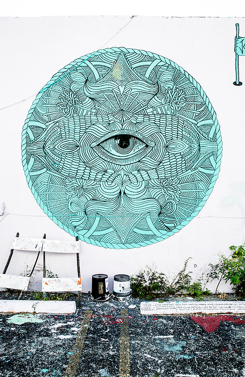 A mandala with a central eye painted on a parking lot wall in Miami's Wynwood arts district