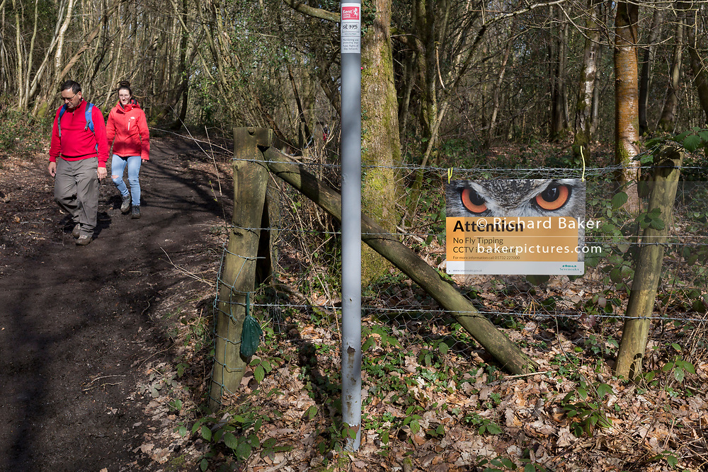 Walkers on a bridleway with a sign warning fly-tippers of CCTV coverage on a rural lane in Kent, on 19th March 2019, in Westerham, England.