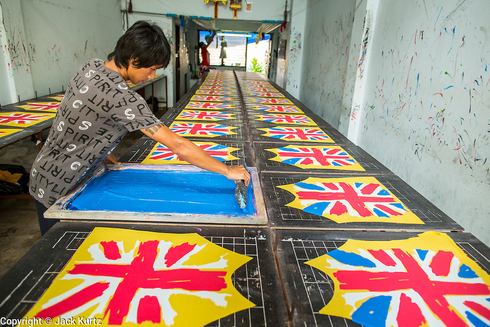 """30 SEPTEMBER 2012 - BANGKOK, THAILAND: Workers screen the """"Union Jack"""" on clothing in a shop in the Raminthra section of Bangkok, Thailand.    PHOTO BY JACK KURTZ"""