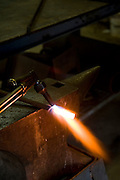Old style hand made iron workers in a small work shop, force shaping a red hot iron rod heating the rod with a blowtorch