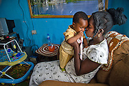 An HIV positive hospital worker in Kaduna Nigeria plays with her young son, who is 7 months old.  This area has a high AIDS rate.
