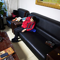 Beijing, March 11 : Tian Peng, 15, is lying on the sofa while his mother Cui Xinying works in the kitchen.<br />